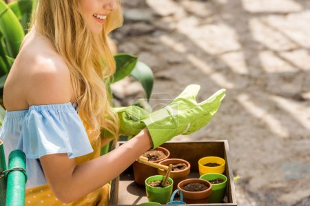 cropped shot of smiling blonde woman in rubber gloves growing plants in greenhouse