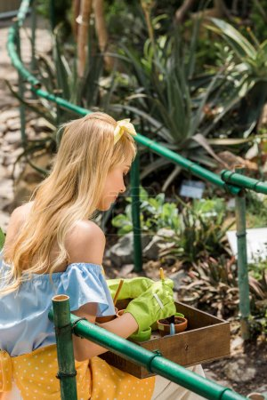 beautiful young woman in rubber gloves growing plants in greenhouse