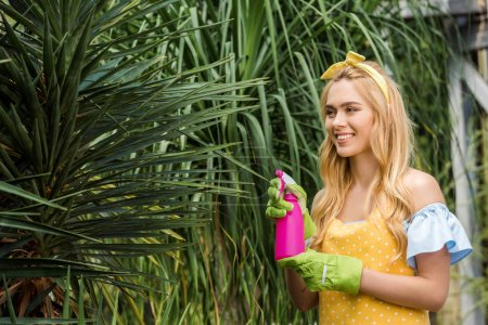 attractive smiling blonde woman holding sprayer and watering green plants