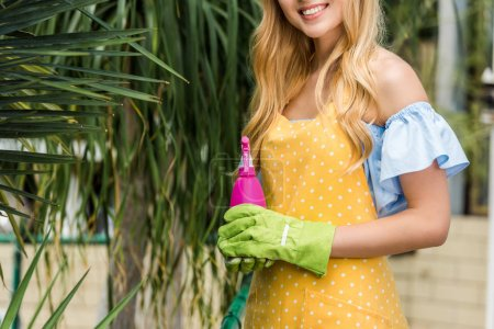 cropped shot of smiling blonde woman in rubber gloves holding sprayer in greenhouse