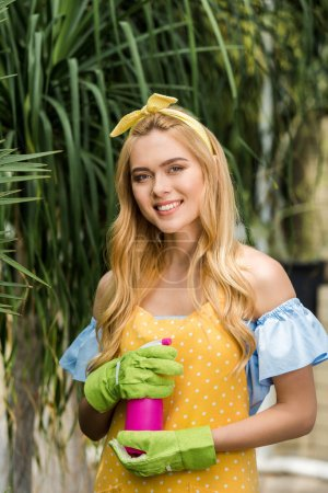 beautiful young woman in rubber gloves holding sprayer and smiling at camera in greenhouse