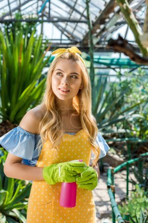 beautiful blonde girl in rubber gloves holding sprayer and looking away in greenhouse