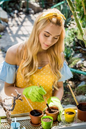 beautiful young blonde woman working with flower pots and gardening tools in greenhouse