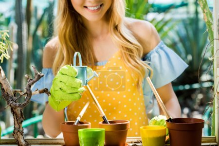 cropped shot of smiling girl holding small watering pot while working with flower pots and gardening tools