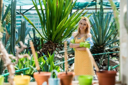 beautiful blonde girl in rubber gloves standing with crossed arms and smiling at camera in greenhouse