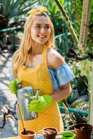 beautiful smiling young woman holding watering pot and looking away in greenhouse