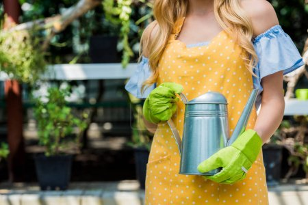 cropped shot of young woman in rubber gloves holding watering can in greenhouse