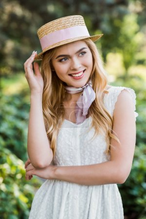 beautiful tender blonde girl in dress and wicker hat with ribbon smiling and looking away in park
