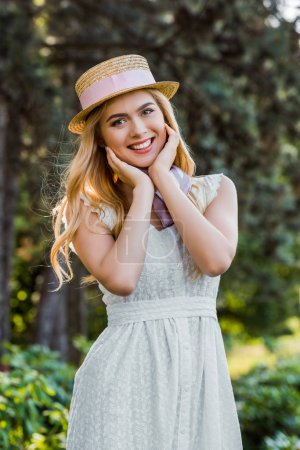 beautiful tender blonde girl in dress and wicker hat with ribbon smiling at camera in park