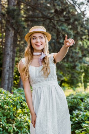 beautiful smiling girl in white dress and wicker hat with ribbon pointing away with finger in park
