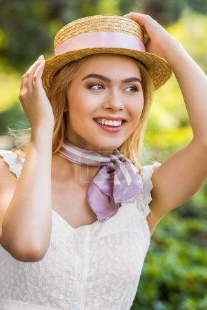 Photo for Beautiful smiling blonde girl wearing wicker hat with ribbon and looking away in park - Royalty Free Image