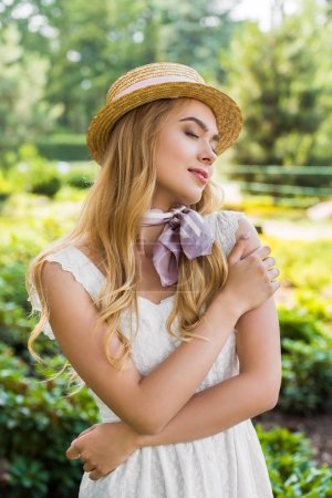 Photo for Beautiful tender young woman in dress and wicker hat standing with closed eyes in park - Royalty Free Image