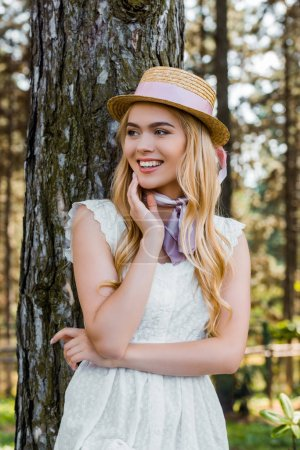 beautiful blonde girl in wicker hat with ribbon standing near tree and looking away