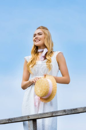 beautiful smiling blonde girl holding wicker hat with ribbon and looking away against blue sky