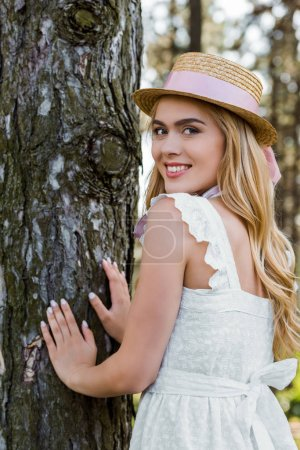 beautiful young woman in wicker hat touching tree and smiling at camera