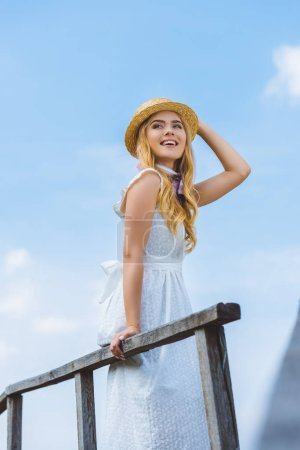 low angle view of happy blonde girl in wicker hat smiling and looking away against blue sky