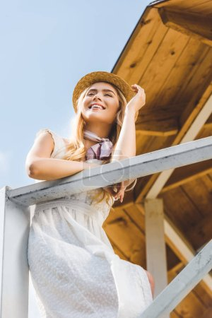 low angle view of happy girl in white dress and wicker hat leaning at railing at sunny day