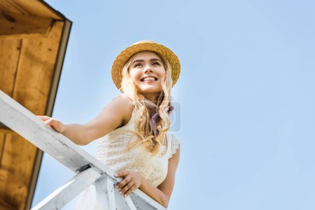 low angle view of beautiful happy blonde girl in wicker hat leaning at railing and looking away against blue sky