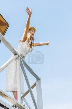 low angle view of cheerful young woman in dress and wicker hat raising hands and looking away against blue sky