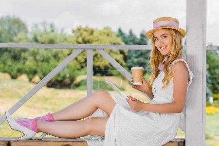 hermosa chica en vestido blanco y sombrero de mimbre sosteniendo taza de papel y el uso de tableta digital mientras está sentado en el banco y sonriendo a la cámara en el parque