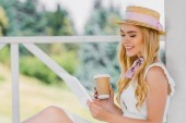 side view of beautiful smiling blonde girl in wicker hat holding coffee to go and using digital tablet