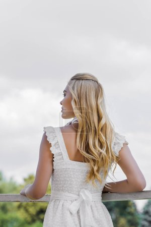 back view of beautiful young blonde woman in white dress looking away in park