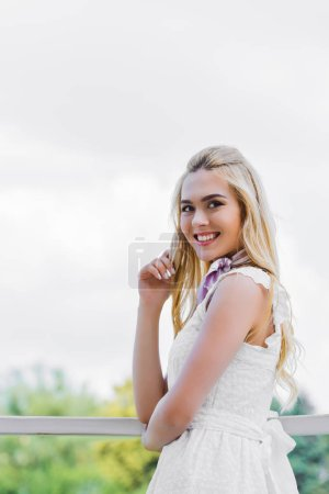 beautiful young blonde woman in white dress smiling at camera