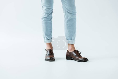Cropped view of male legs in oxford shoes and jeans on white background