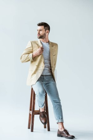 Handsome bearded man in beige jacket sitting on stool on white background