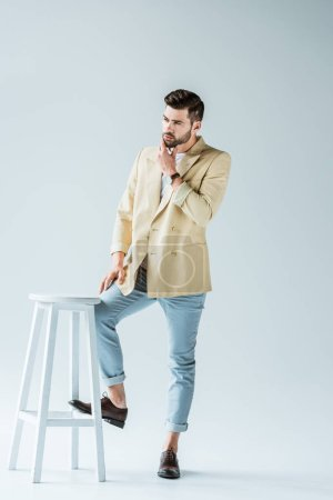Handsome bearded man leaning on stool on white background