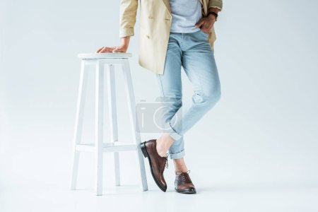 Cropped view of stylish young man standing by white stool on white background