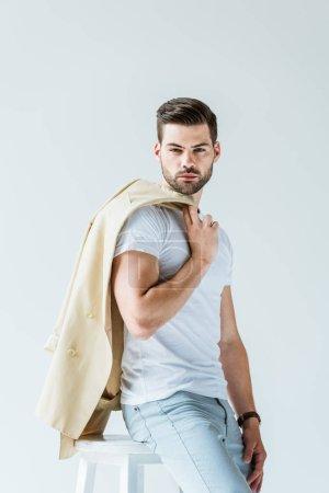 Fashionable confident man holding his jacket isolated on white background
