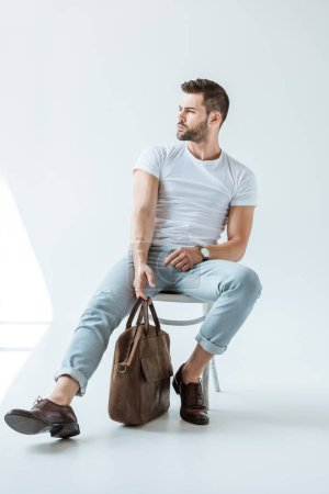 Photo for Stylish young man sitting on chair and holding briefcase on white background - Royalty Free Image