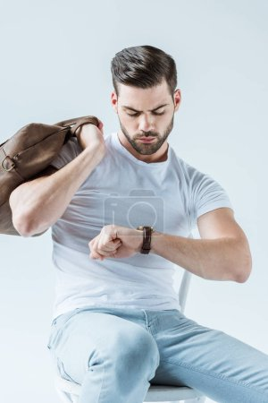 Handsome bearded man holding briefcase and checking his watch isolated on white background