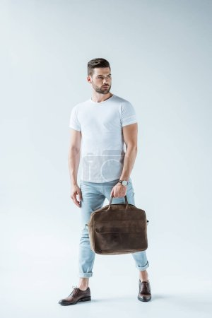 Stylish young man carrying briefcase on white background