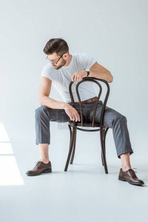 Fashionable confident man in glasses sitting on chair on white background