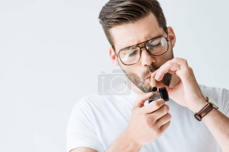 Handsome bearded man in glasses lighting cigar isolated on white background