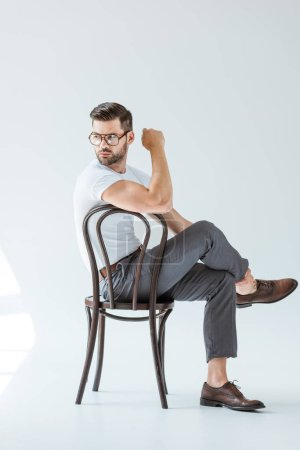 Photo for Stylish young man in glasses sitting on chair on white background - Royalty Free Image