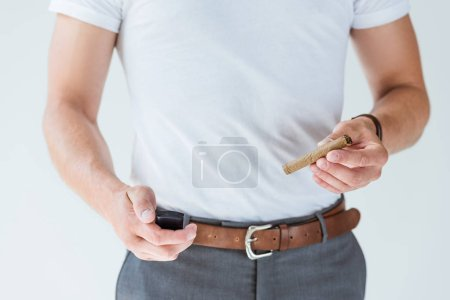 Cropped view of male hands with cigar and lighter isolated on white background