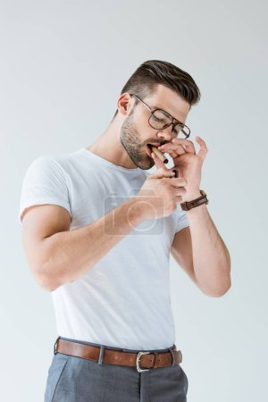 Fashionable confident man lighting his cigar isolated on white background