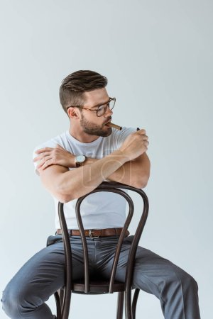 Handsome bearded man lighting his cigar while sitting on chair isolated on white background