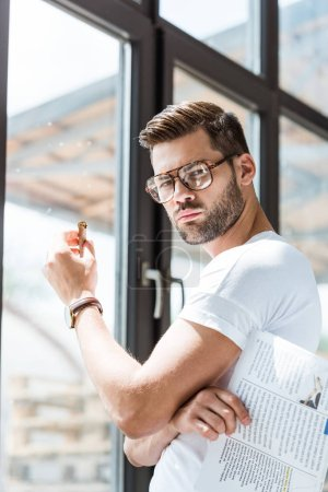 Photo for Stylish young man holding cigar and standing by window - Royalty Free Image