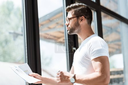 Handsome bearded businessman in glasses reading report by window
