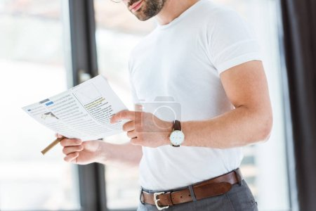 Stylish young businessman reading business report and holding cigar by window
