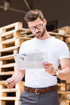 Handsome bearded businessman holding cigar and reading report by wooden palettes
