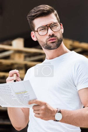 Fashionable confident businessman reading business document and holding cigar by wooden palettes
