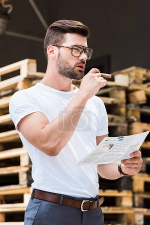 Handsome bearded businessman  in glasses smoking cigar while reading business report by wooden palettes