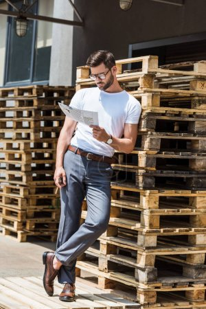 Fashionable confident businessman smoking cigar and reading report by wooden palettes