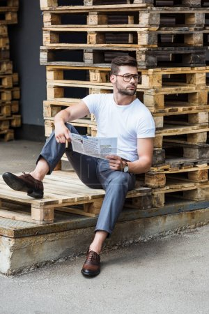 Handsome bearded businessman sitting on wooden palettes with cigar and report in hands