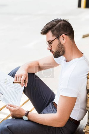 Stylish young businessman reading business document and smoking by wooden palettes